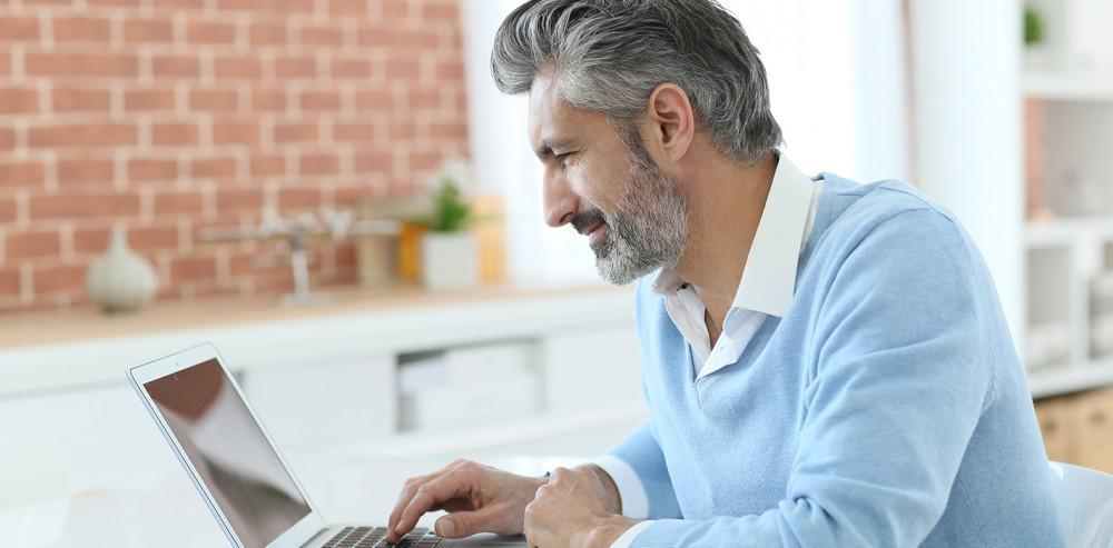 attractive silver haired bearded man on laptop