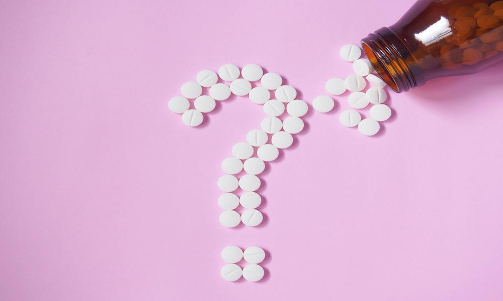 pills in a question mark shape on a pink table